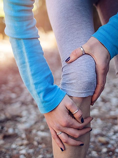Eine Joggerin hält ihr schmerzendes Knie