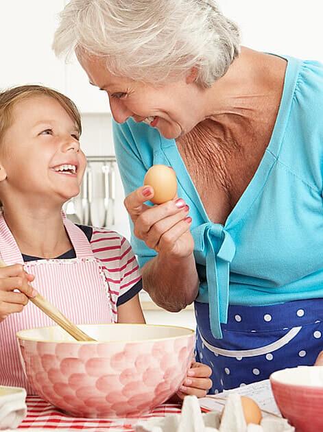Zuckerfrei-Oma und Enkeltochter stehen lachend in der Küche und backen zusammen
