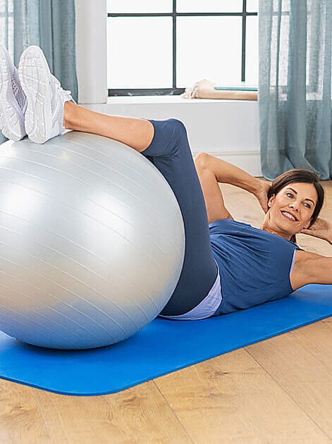 Fitness zu Hause: Frau um die fünfzig liegt auf einer Yogamatte, die Beine auf einem Gymnastikball und trainiert