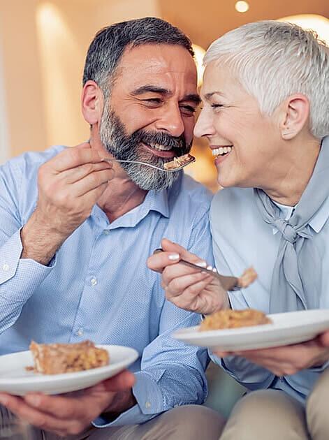 Süßigkeiten - Älteres Ehepaar sitzt auf der Couch und ist genüsslich Kuchen