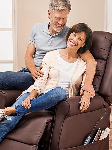 Älteres Ehepaar sitzt zufrieden und umschlungen auf einem Massagesessel