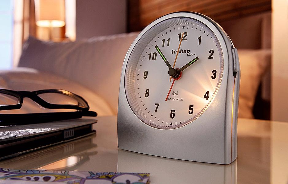 Beleuchteter analoger Funkwecker für daheim oder auf Reisen steht auf dem Nachttisch