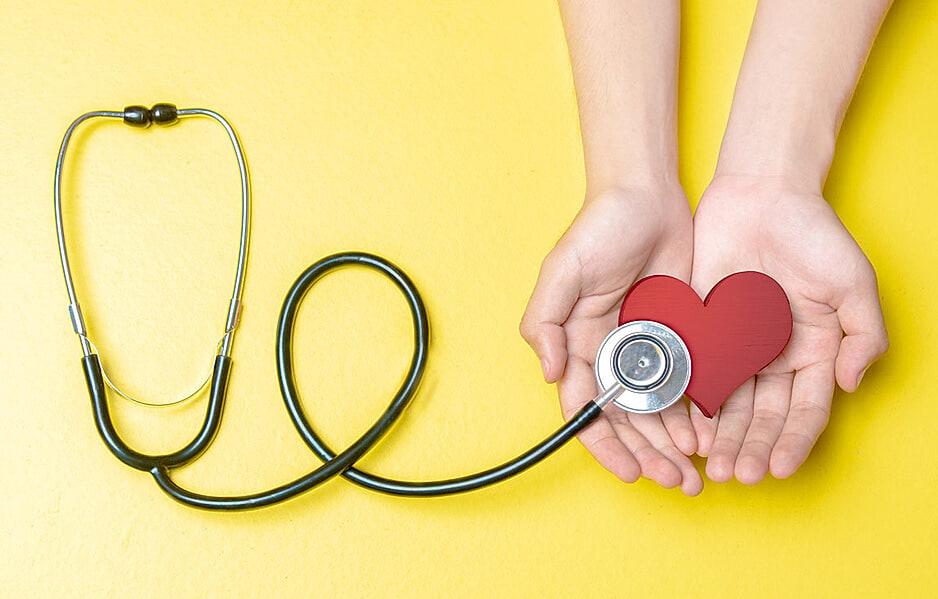 Herzinfarkt - zwei Hände halten ein Stoffherz, das von einem Stethoskop abgehört wird