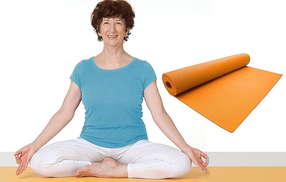 Yoga - ältere Frau sitzt auf Yogamatte und macht Übungen