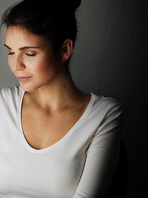 Lichttherapie - Eine Frau sitzt vor einer Tageslichtlampe