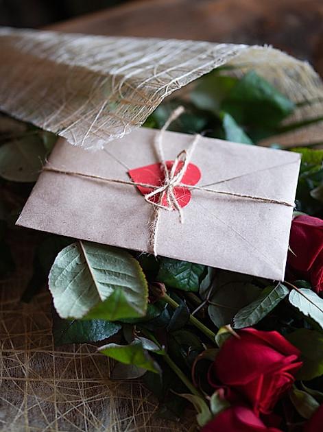 Geschenke zum Valentinstag: Klassiker unter den Liebesbezeugungen: rote Rosen und ein Liebesbrief.