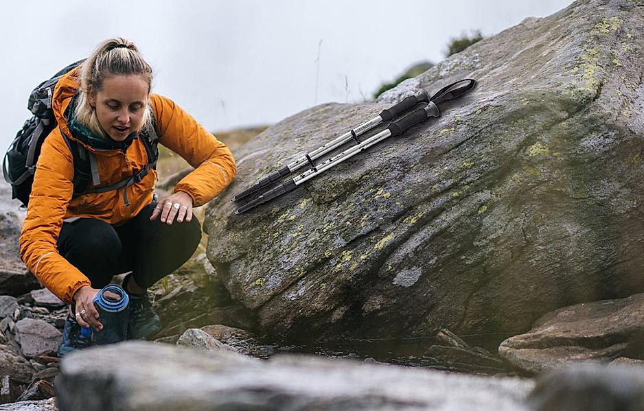 Frau ist in den Bergen unterwegs mit Trekkingstöcken und füllt ihre Wasserflasche auf