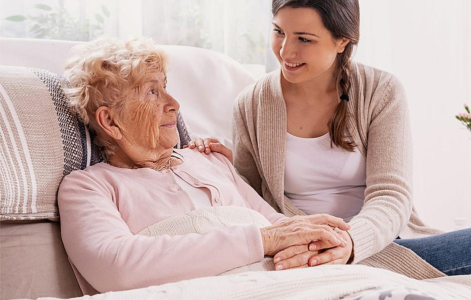 Enkeltochter sitzt bei ihrer pflegebedürftigen Großmutter am Bett und hält deren Hand