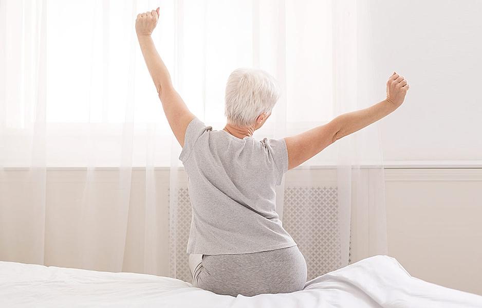 Ältere Frau sitzt auf Ihrem Bett und streckt sich genüsslich