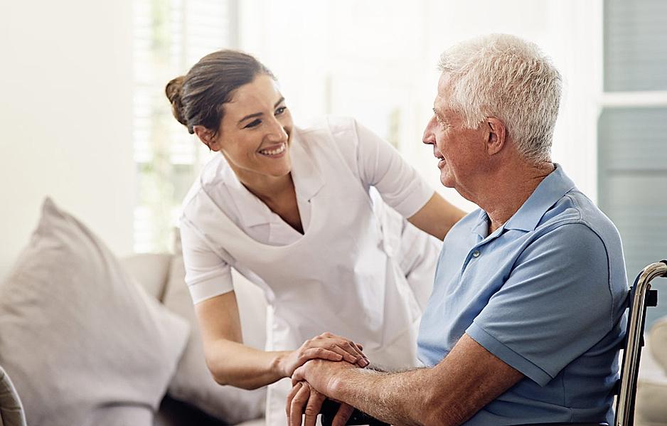 Pflegekraft kümmert sich um älteren Patienten in der häuslichen Pflege