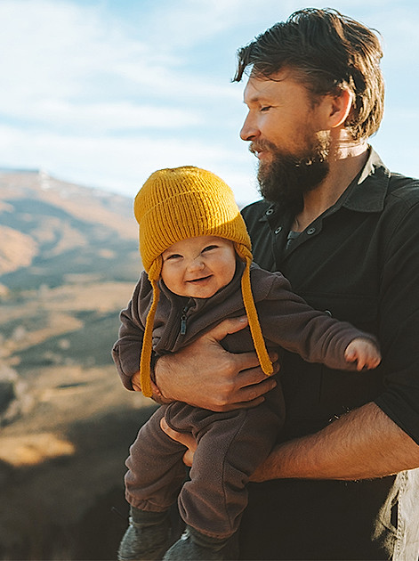 Kuschelig eingepackt: Papa mit dem Nachwuchs