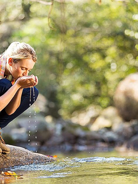 Junge Frau trinkt mit den Händen frisches Wasser vom Bach