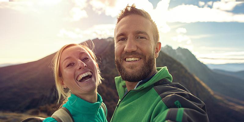 Paar mit Wanderausrüstung auf Berggipfel
