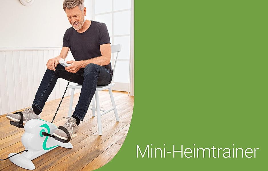 Ältere Mann trainiert zuhause mit einem Mini-Heimtrainer