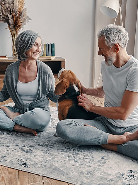 Mann und Frau sitzen im Schneidersitz und praktizieren Entspannungstechniken - Orbisana Ratgeber