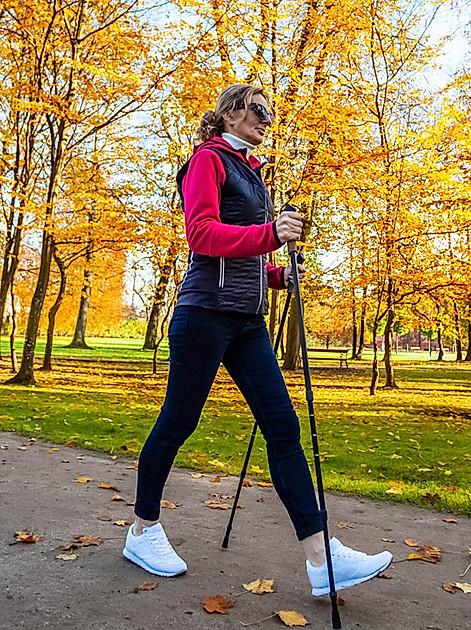 Frau betreibt draußen im Herbst Nordic Walking - Orbisana Ratgeber