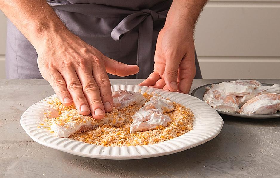 5. Auf einem flachen Teller 80 g Semmelbrösel mit 50 g fein zerstoßenen Cornflakes mischen (siehe Text oben). Die Hähnchenstücke in der Mischung wenden, dabei die Panade nicht zu fest andrücken.