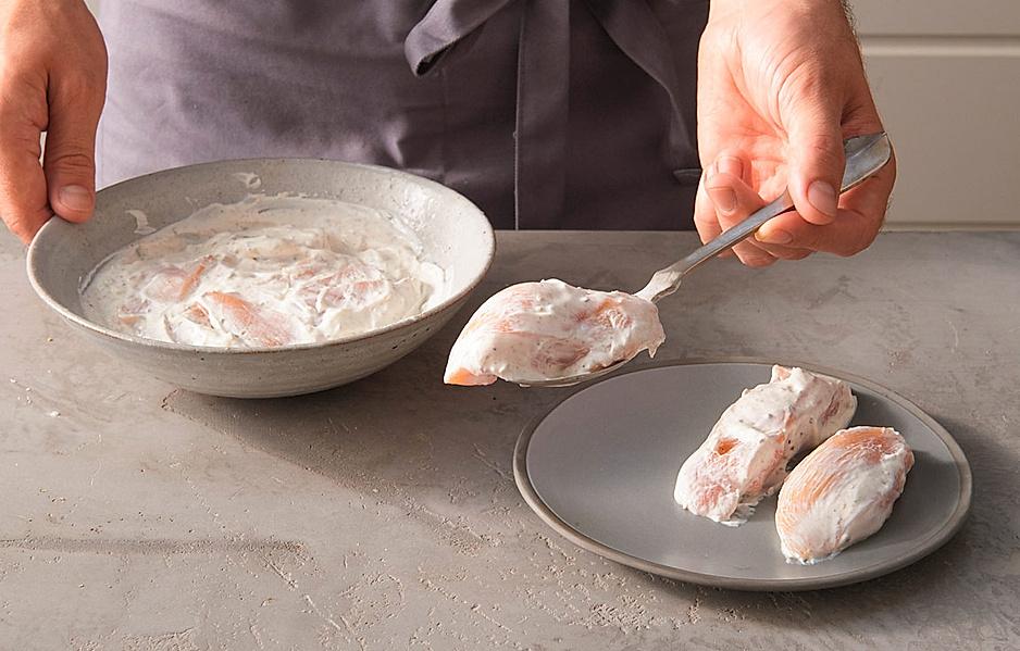 4. Die Hähnchenstücke aus der Marinade nehmen und den Gewürzjoghurt leicht von den Hähnchenbruststücken abstreifen. Das Fleisch mit Salz würzen.